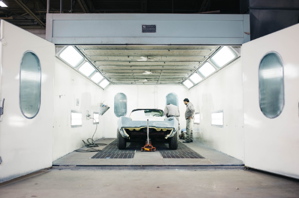 A car, mid-production, in a hangar with two technicians working on it.