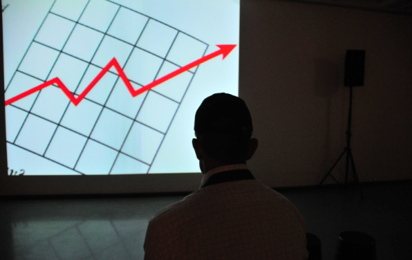 A man looking at a graph on a projector screen.